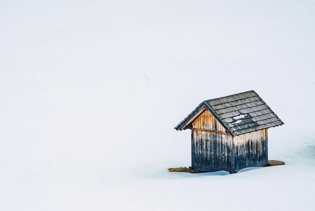 Kleine holzscheune in einem schneebedeckten feld