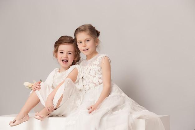 Kleine hübsche mädchen mit blumen in brautkleidern gekleidet.