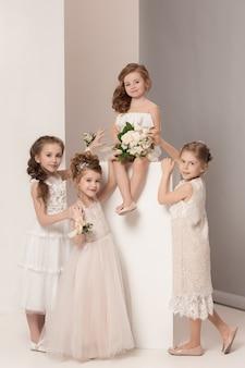 Kleine hübsche mädchen mit blumen in brautkleidern gekleidet