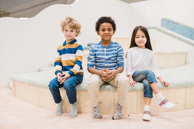 Kleine interkulturelle gruppe von niedlichen kleinen kindern, die vor der kamera im modernen spielzentrum für kinder sitzen