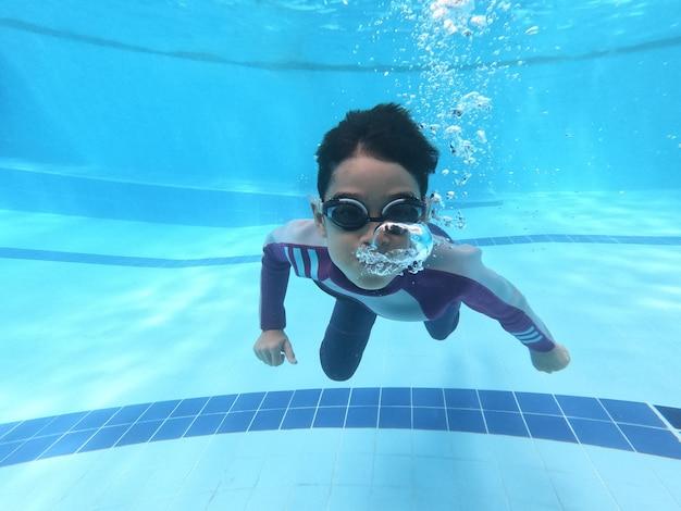 Kleine jungen, die am pool unter wasserschuß schwimmen und tauchen
