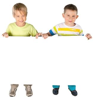 Kleine jungen, die ein leeres poster auf weißem hintergrund halten