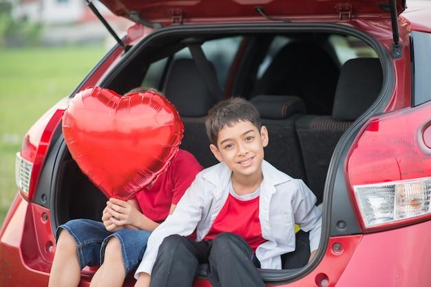 Kleine jungen, die in der hand auf der hintertür des autos mit ballonherzen sitzen
