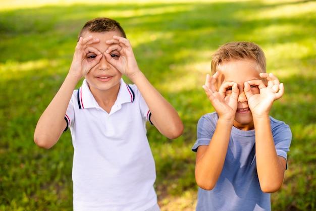 Kleine jungen, die mit ihren fingern gefälschte gläser herstellen