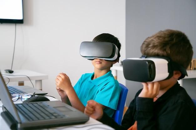 Kleine jungen, die vr-headset verwenden und mit laptop am tisch sitzen