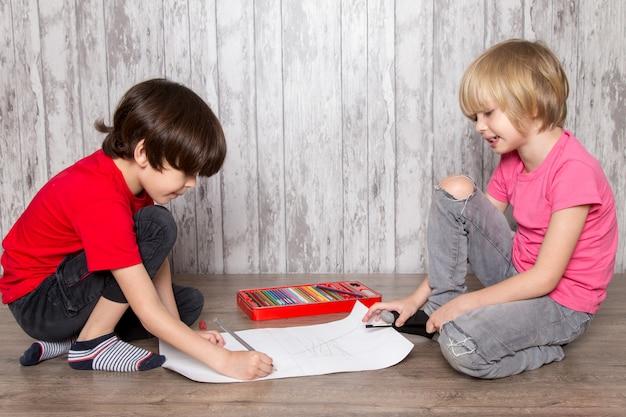 Kleine jungen in rosa und roten t-shirts zeichnen