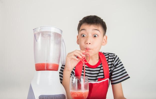Kleine jungen mischen wassermelonesaft, indem sie mixer zu hause verwenden