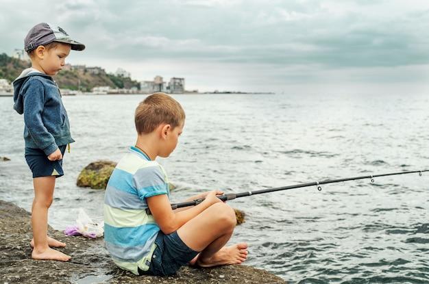 Kleine jungen mit angelrute am strand, zwei kleine fischer, die gerne angeln
