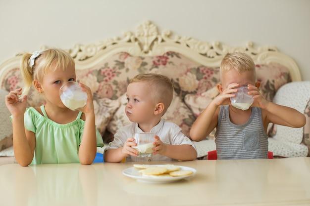 Kleine jungen und mädchen trinken milch am tisch