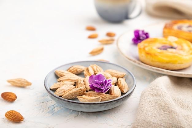 Kleine käsekuchen mit marmelade und mandeln mit tasse kaffee auf weißem beton