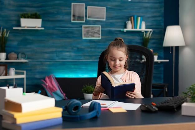 Kleine kaukasische studentin, die buchleseseiten für den schularbeitsunterricht in der online-internetklasse hält. intelligentes mädchen, das das wissen für das konzept und die prüfung des bildungsfortschritts verbessert