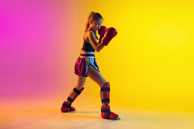Kleine kaukasische weibliche kickboxertraining auf gradientenhintergrund im neonlicht, aktiv und ausdrucksstark
