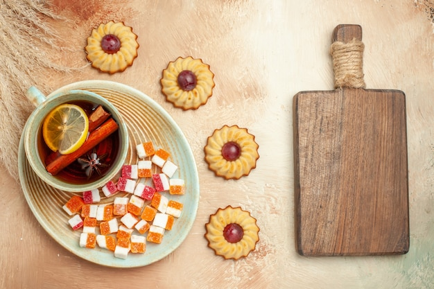 Kleine kekse der draufsicht mit tasse tee auf braunem tisch, süßes kuchendessert des kekses