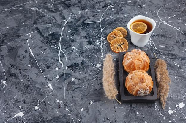Kleine kekse profitroles mit zuckerpulver und zimtstangen.