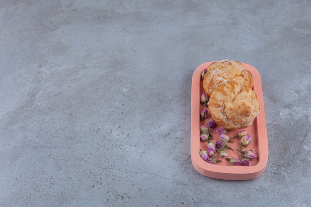 Kleine kekse profitrollen mit getrockneten rosenknospen.