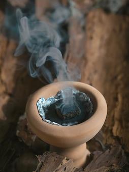 Kleine keramik dekorative arabische bakhoor weihrauchbrenner räuchergefäß mit rauch und holz hintergrund.