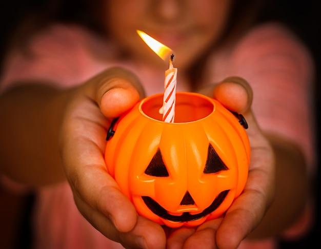 Kleine kerze in orange kerzenhalter kürbis halloween auf kinderhänden