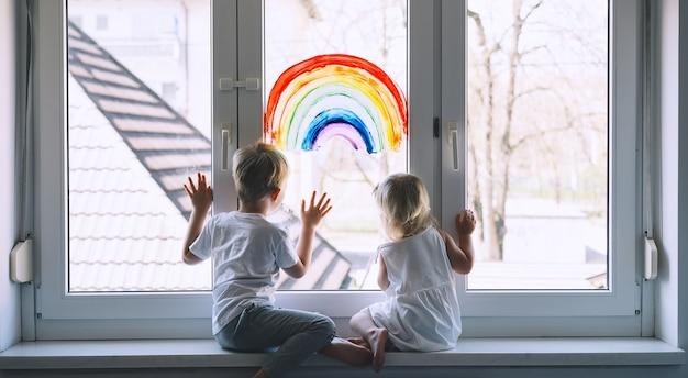 Kleine kinder auf dem hintergrund der malerei regenbogen auf dem fensterfoto der kinderfreizeit zu hause