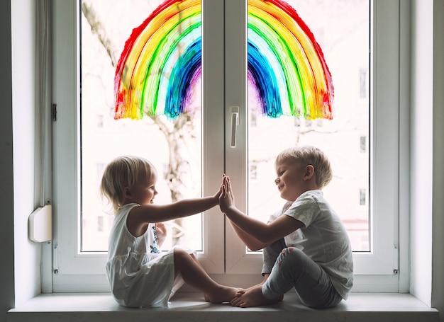 Kleine kinder auf dem hintergrund des malens von regenbogen auf dem fenster positive visuelle unterstützung