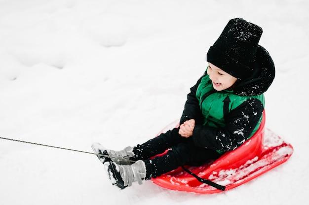 Kleine kinder auf schlitten, die im winterpark spazieren gehen. nahansicht. porträt glückliche kinder.