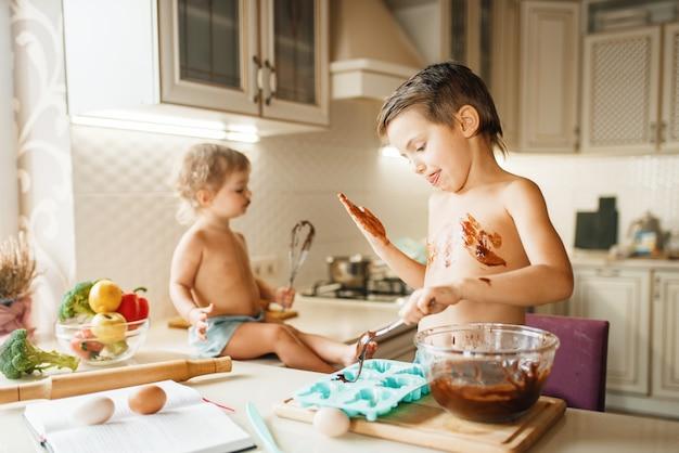 Kleine kinder bereiten gebäck mit geschmolzener schokolade zu.