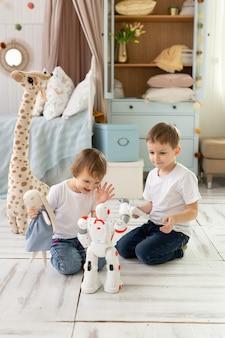 Kleine kinder, bruder und schwester, sitzen auf dem boden im raum, lachen und spielen mit dem roboter