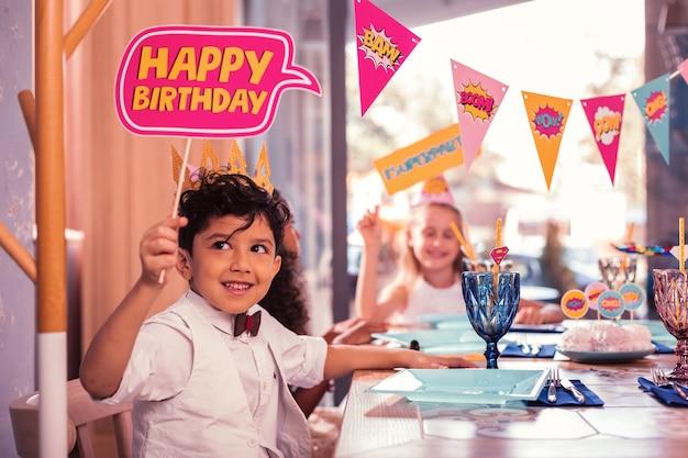Kleine kinder, die eine geburtstagsfeier besuchen und am tisch sitzen