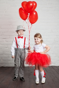 Kleine kinder, die herzballons halten und aufheben. valentinstag und liebeskonzept, auf weißem hintergrund