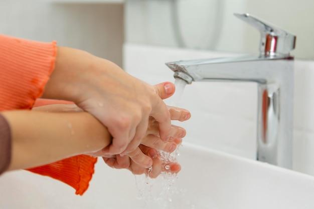 Kleine kinder, die ihre hände nahaufnahme waschen