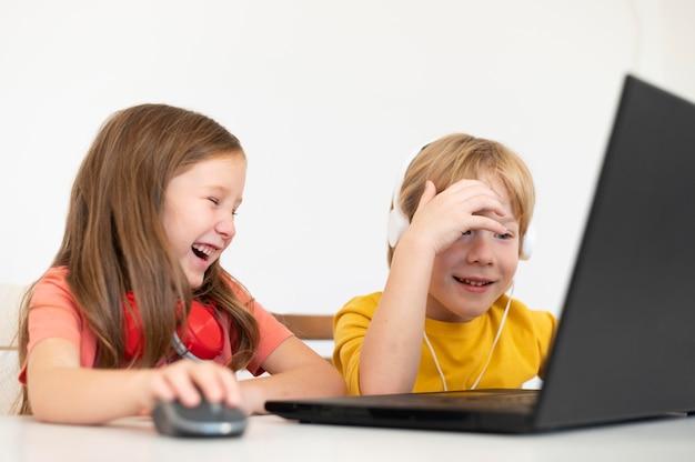 Kleine kinder, die laptop zusammen benutzen