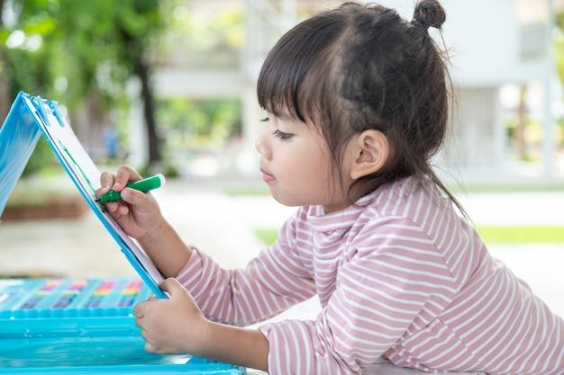 Kleine kinder, die mit einem buntstift zeichnen, sind eine gute aktivität, um die kreativen kunst- und handschriftfähigkeiten von kindern zu verbessern. konzeptbild für bildung und lernhobby.