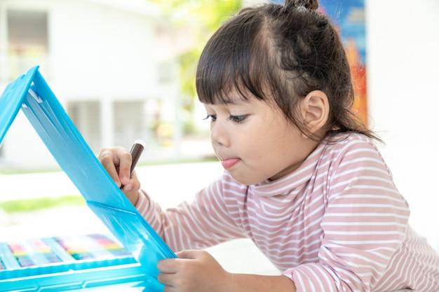 Kleine kinder, die mit einem buntstift zeichnen, sind eine gute aktivität, um die kreativität zu verbessern