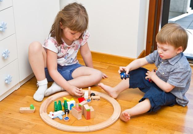 Kleine kinder, die mit hölzernem zug im raum spielen