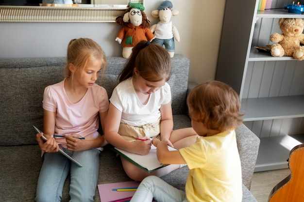Kleine kinder, die zu hause zusammen zeichnen