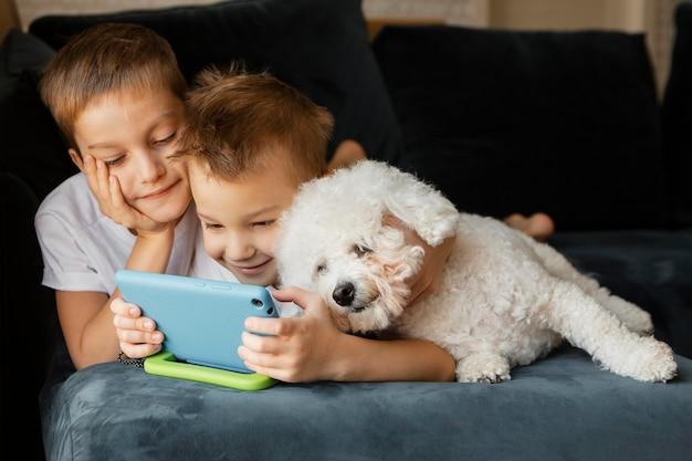 Kleine kinder, die zusammen am telefon schauen
