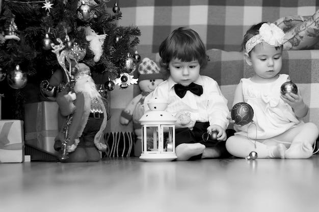 Kleine kinder in der nähe eines weihnachtsbaums vor den feiertagen Premium Fotos