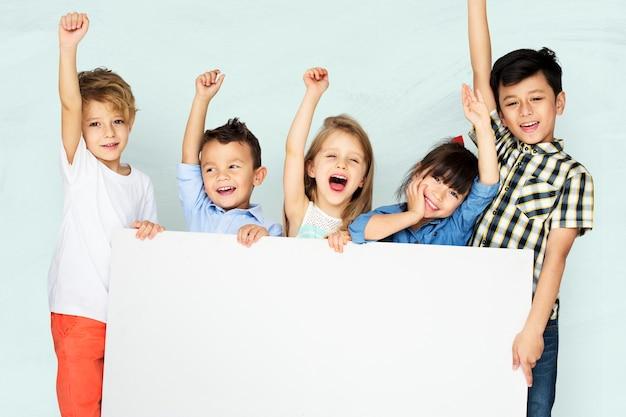 Kleine kinder jubeln, während sie eine weiße tafel halten