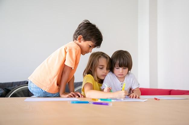 Kleine kinder malen mit markierungen im wohnzimmer. nettes blondes mädchen, das bruder hält. schöne kinder, die am tisch sitzen, auf papier zeichnen und zu hause spielen. kindheit, kreativität und wochenendkonzept