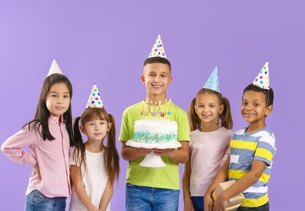 Kleine kinder mit geburtstagstorte auf farbe