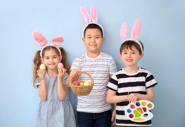 Kleine kinder mit ostereiern und farbpalette auf farboberfläche