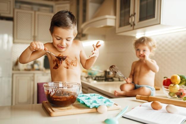 Kleine kinder schmecken geschmolzene schokolade. netter junge und mädchen, die auf der küche kochen.