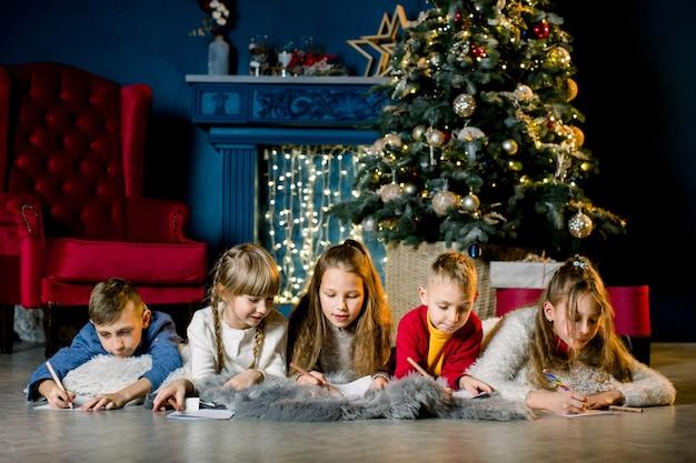 Kleine kinder schreiben einen brief an den weihnachtsmann und erzählen sich gegenseitig weihnachtsgeschichten