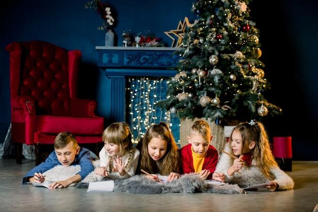 Kleine kinder schreiben einen brief mit wünschen an den weihnachtsmann