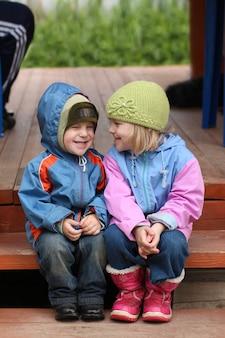 Kleine kinder sitzen auf der treppe des hauses und haben spaß an der kommunikation.