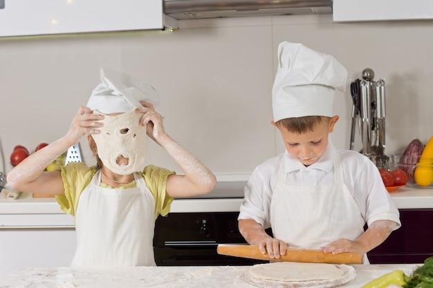 Kleine kinder spielen beim backen in der küche.