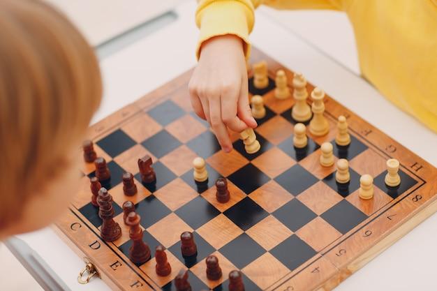 Kleine kinder spielen schach im kindergarten oder in der grundschule