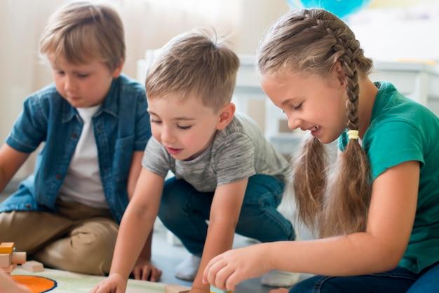 Kleine kinder spielen zusammen im kindergarten