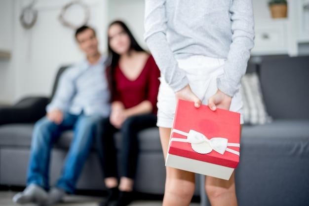 Kleine kinder überraschen ihre eltern mit einer geschenkbox. mama und papa im hauskonzept. familienthema