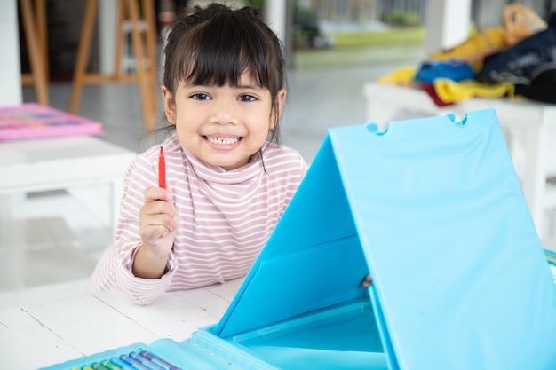 Kleine kinder zeichnen cartoon mit einem farbstift, der eine gute aktivität zur verbesserung der kreativen kunst- und handschriftfähigkeiten bei kindern ist. konzeptbild für bildung und lernhobby.
