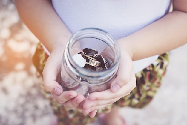 Kleine kinderhände, die münzen halten